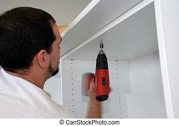 Handyman building cabinet