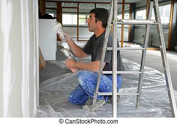 Decorator painting a room