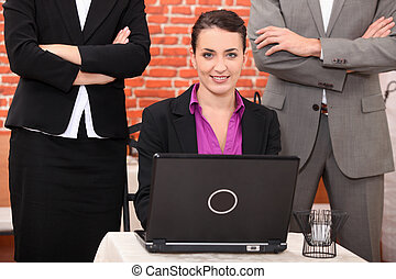 Woman using a laptop in a restaurant flanked by people with...