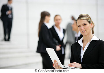 Businesswoman with laptop outdoors