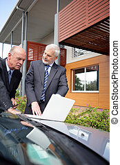 Senior businessmen outside with a laptop