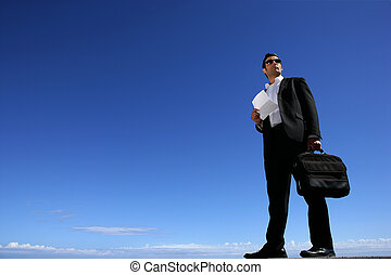 Confident businessman in front of blue sky