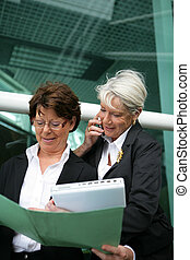 Two senior businesswomen with folders