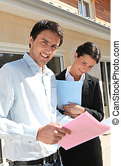 Realty promoters standing in front of a house