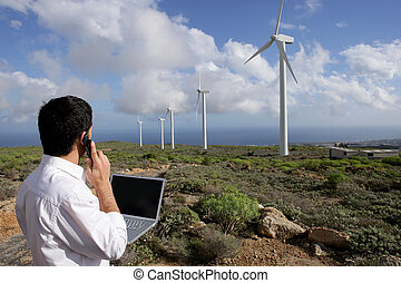 Young businessman on phone next to wind turbines