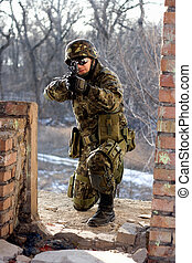 Soldier sitting near wall with a gun