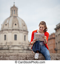 Pretty young female tourist studying a map at the Trajans...