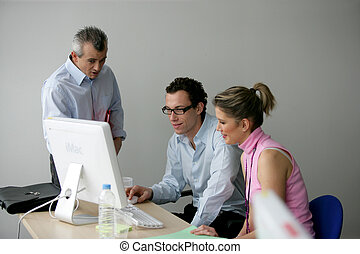 Three colleagues looking at computer screen
