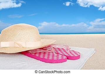 straw hat sandals on a beach towel - closeup straw hat...