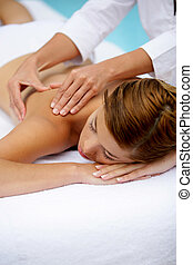 Woman receiving a poolside back massage