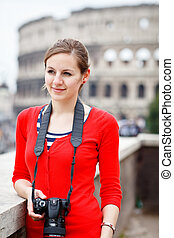 Portrait of a pretty young tourist taking photographs while...