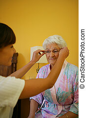 Woman helping old lady with eyeglasses