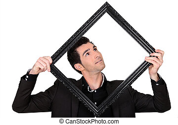 a man looking a wooden frame