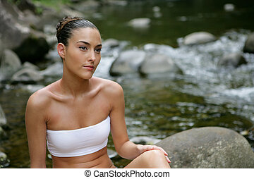 Attractive woman bathing by the river