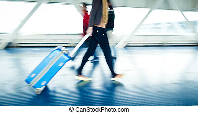Airport rush: people with their suitcases walking along a...