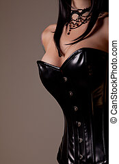 Busty woman in black corset, studio shot on beige background...