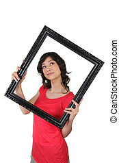 Young woman carrying black frame, studio shot