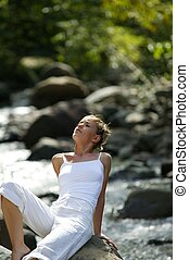 Woman relaxing by stream