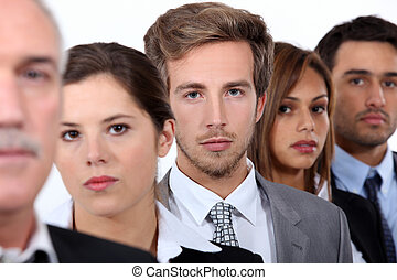 Closeup of the faces of a group of serious young executives...