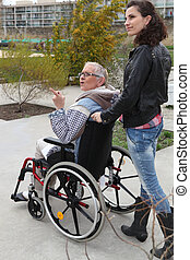 a young woman pushing senior woman in wheelchair