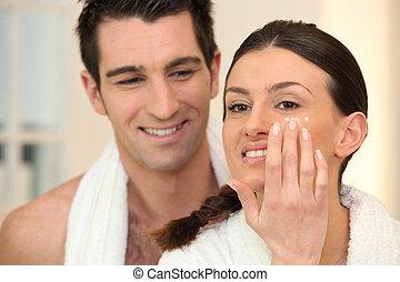 Woman applying under eye cream