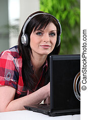 Woman listening to her laptop through headphones