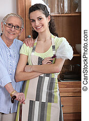 Young woman in an apron with an elderly lady