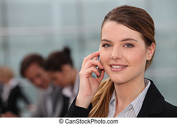 A young woman phoning in an office and looking at us.