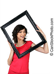 Woman holding herself within a picture frame