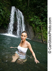 Brunette stood by waterfall
