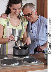 Granddaughter cooking for her grandmother