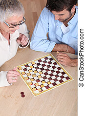 Senior woman playing checkers with a young man