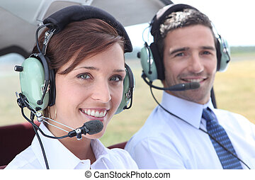 Man and woman wearing headsets in the open cockpit of a...