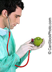 doctor examining an apple with a stethoscope