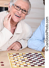 An old laughing lady playing checkers with somebody.