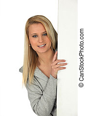Young woman peeking out from behind a wall