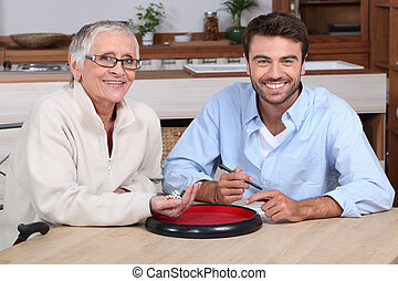 An elderly lady and a young bearded man playing dice and...