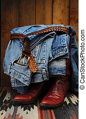Blue Jeans draped over Cowboy Boots - Denim blue jeans tied...