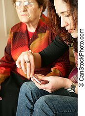 Young woman manicuring senior woman