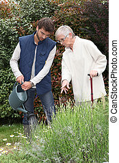 A gardener watering flowers in a garden and an elderly lady...