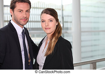 Business couple in front of window