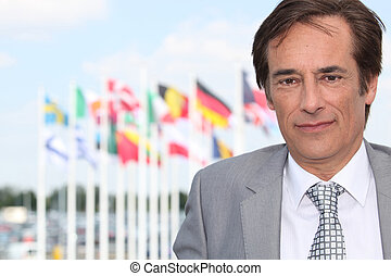 Businessman in front of flags