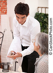 Young waiter serving an older customer rose wine