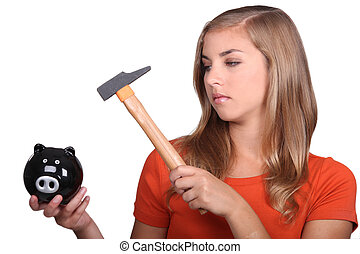 Blond teenage girl smashing piggy bank with hammer