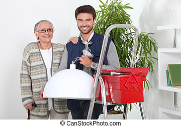 Young man repairing old Lady's lighting