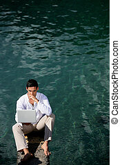 Businessman sat by water