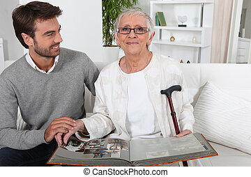Elderly person looking at photos with son