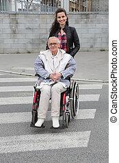 Girl pushing senior woman in wheelchair