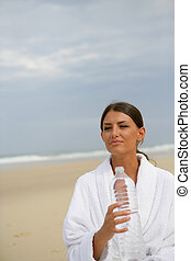 Brunette stood on a beach holding bottle of water