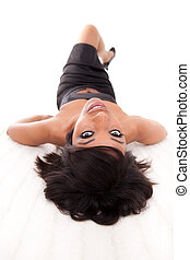 Young beautiful black woman lying down on the floor